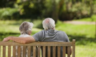 older couple sitting on bench and talking